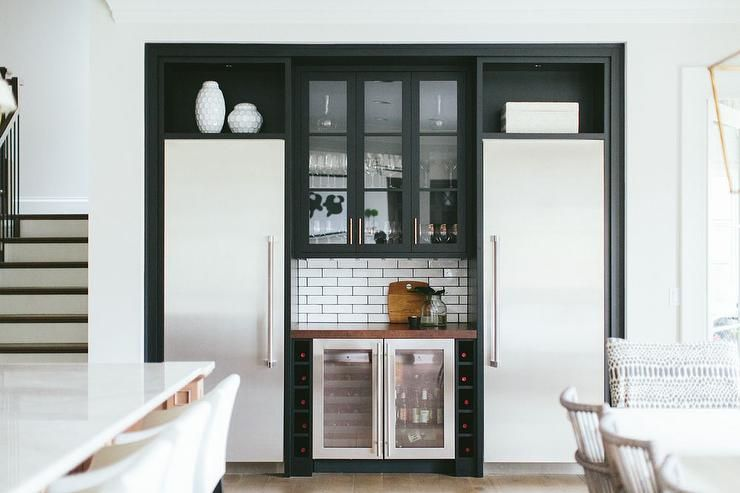 A kitchen alcove is filled with black cabinets with glass doors