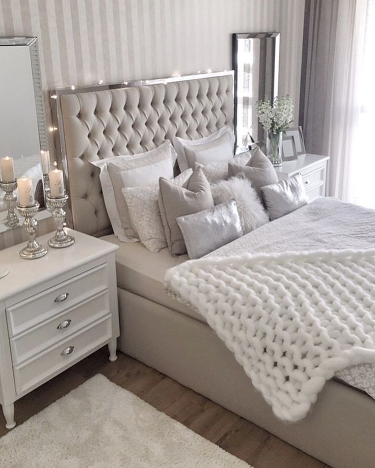 A beautiful romantic bedroom space. There are so many different elements and they all compliment each other perfectly. The various types of pillows and bedding, the bed frame and the striped call behind are all so elegant.