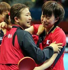 決勝進出を決めた日本の福原(左)と石川は涙を流しながら抱き合う。後方は平野
