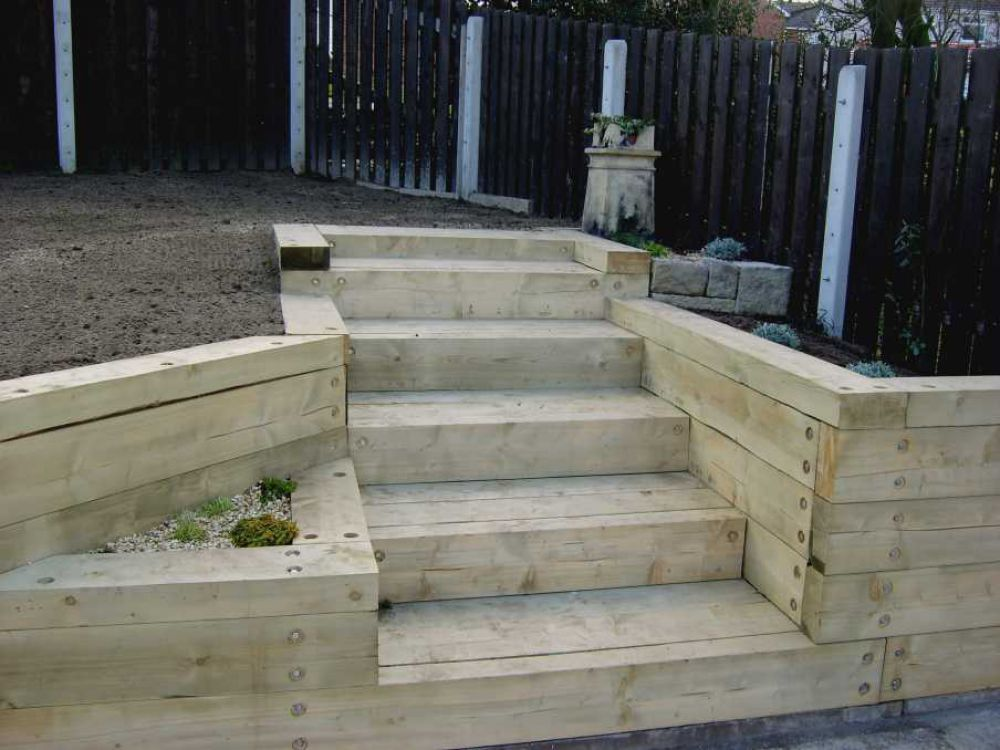 wall made with railroad ties flower beds on both sides with lights on lower steps landscaping design garden
