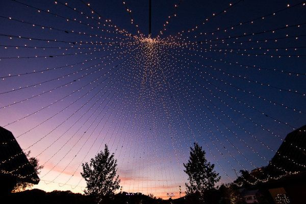 String lights are used to create a canopy tent of soft, glowing lights.