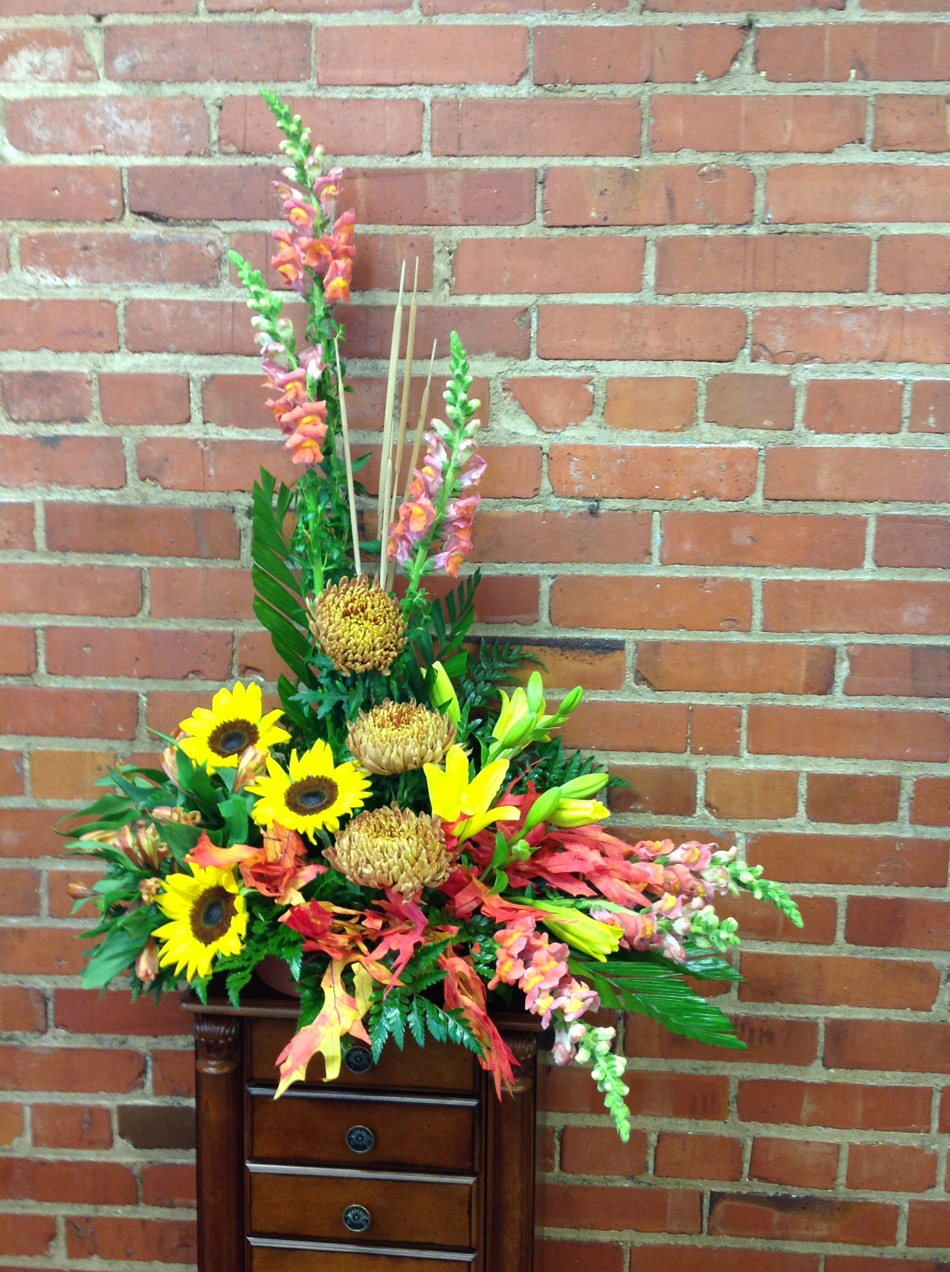 Sunflowers,snapdragons football mums and lilies make this a perfect fall arrangement for a funeral.