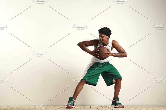 Fit black athlete playing with a vintage basketball. People Photos. $10.00