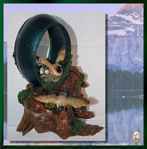 Stands apx. 7 tall. Egg is emu with a deep metallic green exterior. Base is a piece of lacquered driftwood. On the sides of the egg are embossed cattails. Figures of Canada geese are made of parastone. Goose inside of egg is sitting on a nest of eggs.