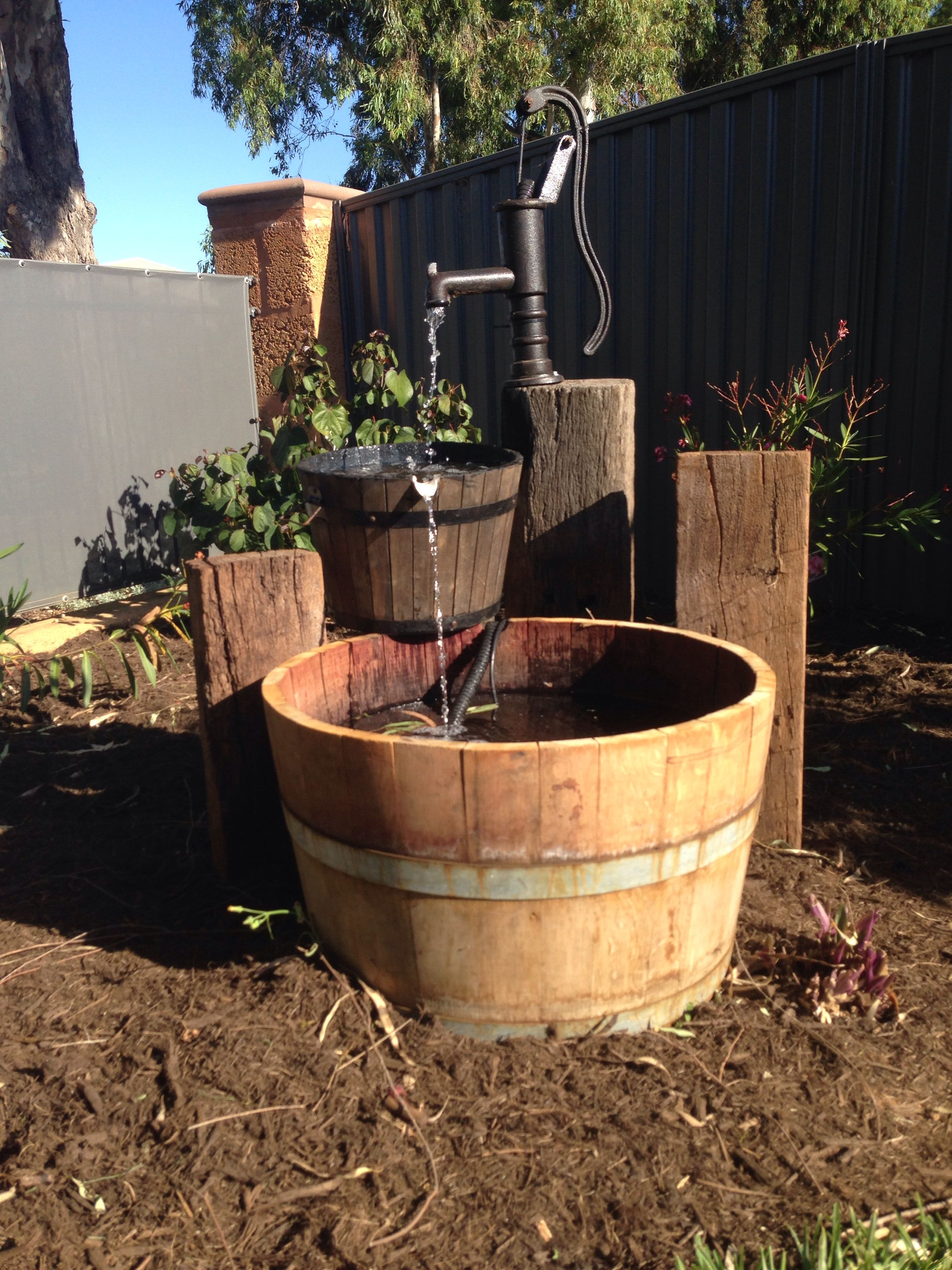 Rustic water feature using an old well pump, wine barrel and railway ...