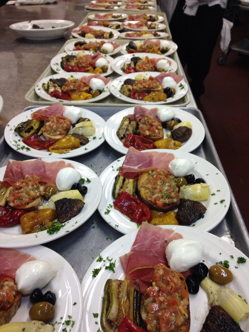 Individual antipasto--bocconcini, prosciutto, bruschetta, olives, sweet peppers, and artichoke hearts.