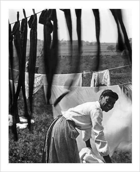 Black and white, an informal portrait of a young Negro woman surrounded by laundry in Newport, Rhode Island. (1902)