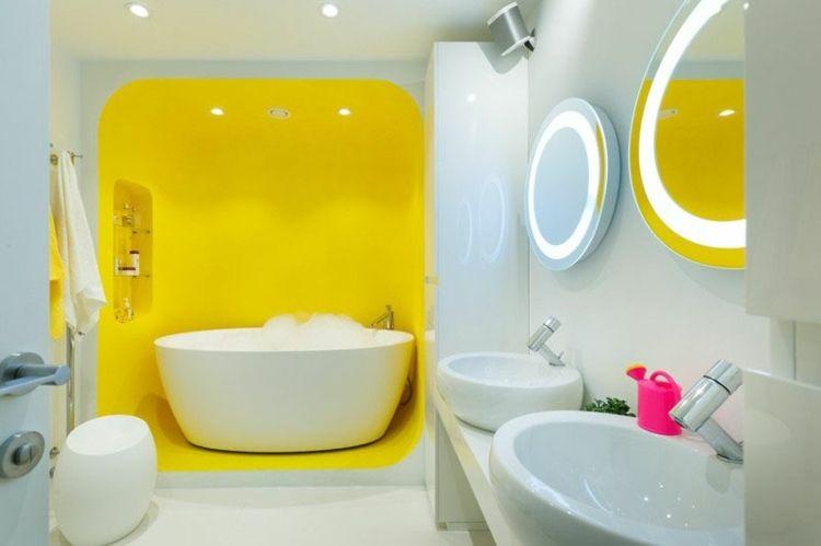peinture jaune, miroirs ronds, tabouret design et baignoire îlot