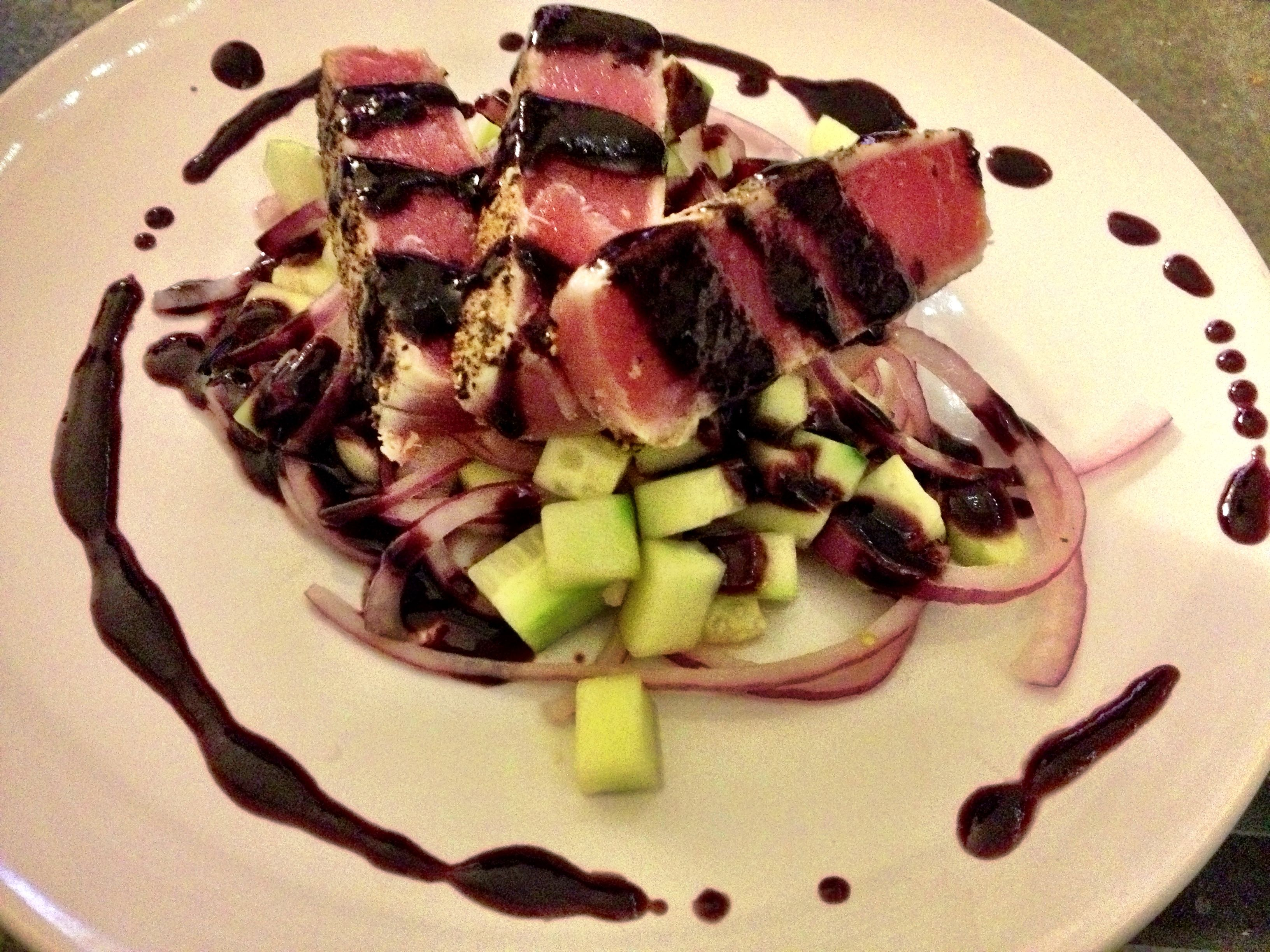 Black pepper crusted seared ahi tuna with a cucumber/red onion salad tossed in a red wine vinegrette. Topped with a balsamic blueberry reduction.