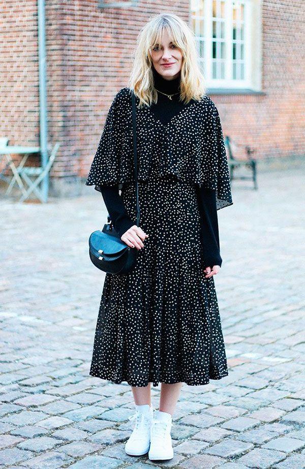 Street style look com vestido de poá sobre turtleneck preta, tênis branco e bolsa preta.