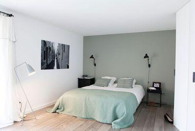 Dans la chambre parentale le mur peint dans un gris presque vert