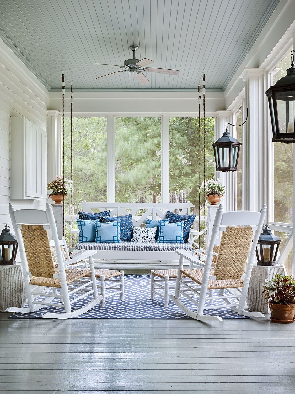A screened porch epitomizes Southern style with a bed swing made in South Carolina and chairs from Georgia. Designer James Farmer finished the look by layering blue-and-white textiles in an assortment geometric and organic patterns. Photo by Emily Followill