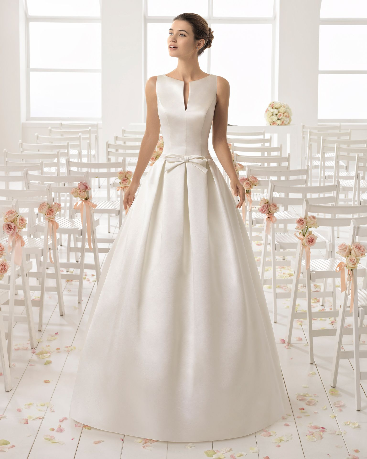 Vestido de noiva estilo clássico de cetim duquesa e decote tipo barco com abertura à frente com laço na cintura em cor marfim.