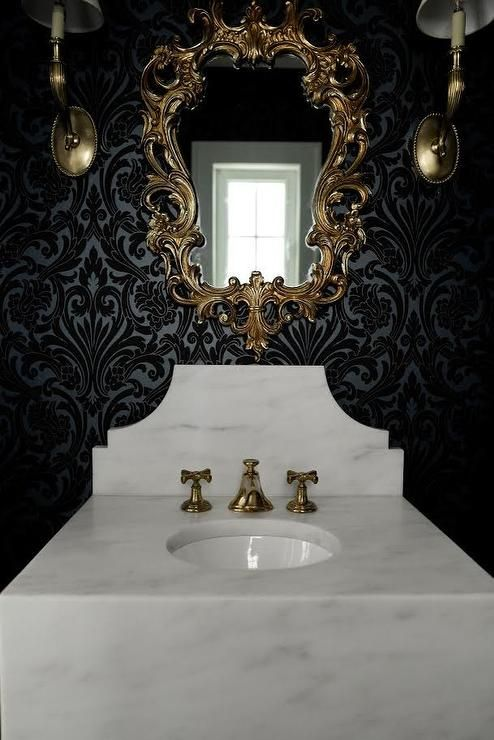 Dramatic yet luxurious black and gold powder room is lit