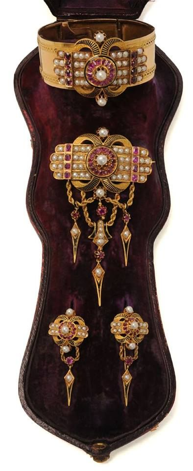 Parure, mid-nineteenth century, comprising bangle, brooch and earrings. Gold, Ruby, Pearl and black Enamel.