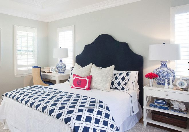 blue and white bedroom with navy headboard. bed is dressed in navy