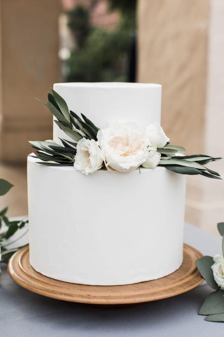 Einfache Hochzeitstorten mit viel Grün geschmückt, Kuchenblumen. Einfach, organisch, weiß …
