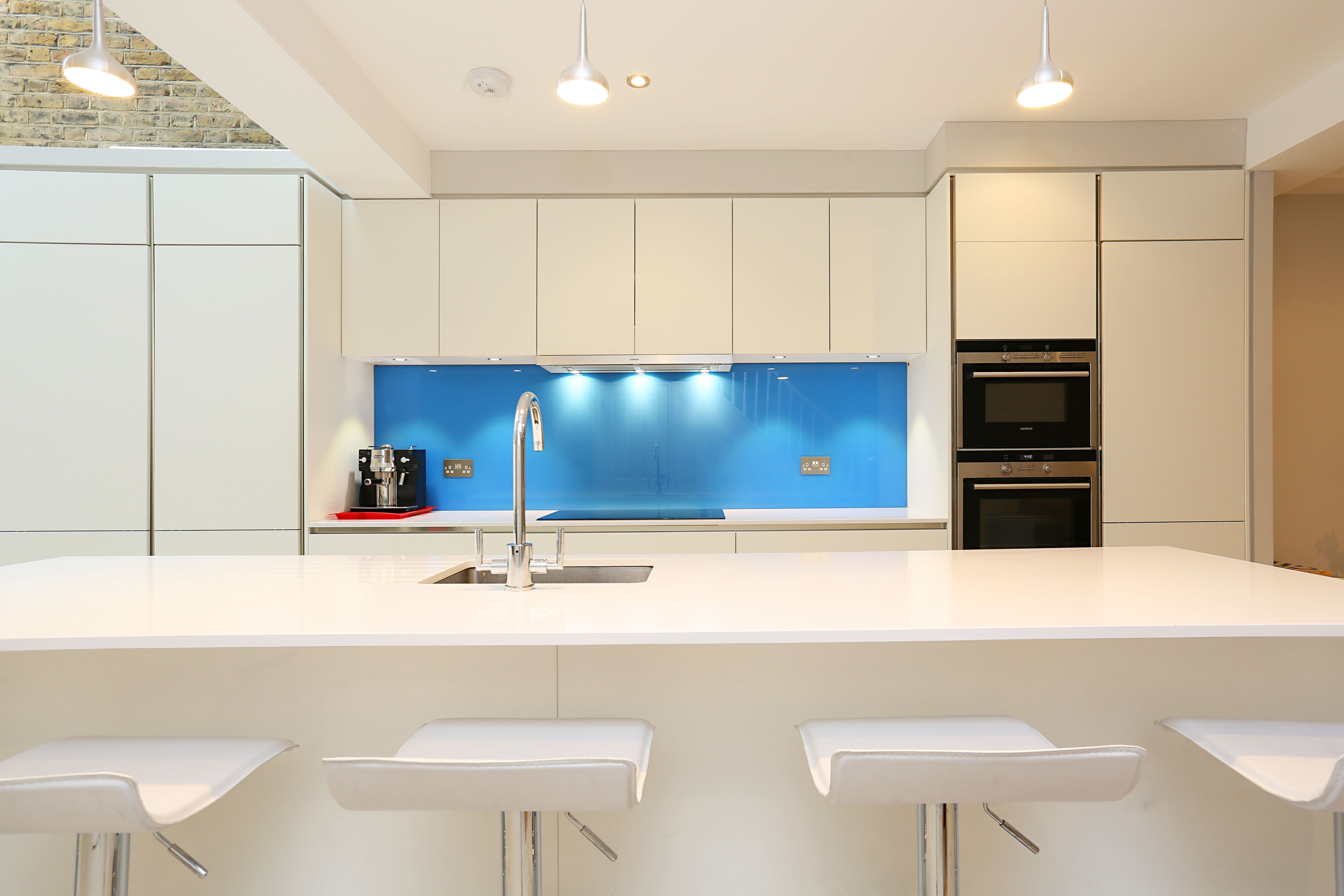 Bright and bold blue splashback. This acts as a great statement in ...