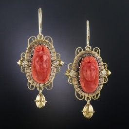 Measuring 1 1/2 inches long and lovely (they drop a bit further from the ear wires), these classic Victorian ear baubles, circa 1875, present a pair of classic beauties hand carved in high relief in rich salmon colored corals. The cameos are magnificently framed in tri-color (yellow, rose & white) 14K gold and support a dancing dangle. Consummate Victoriana.