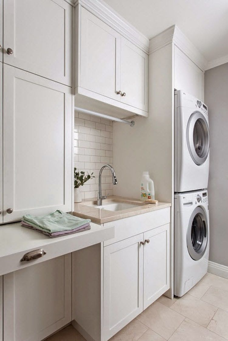 White laundry room features white cabinets adorned with vintage latch  hardware paired with carrera marble countertops and a white subway tile  backs