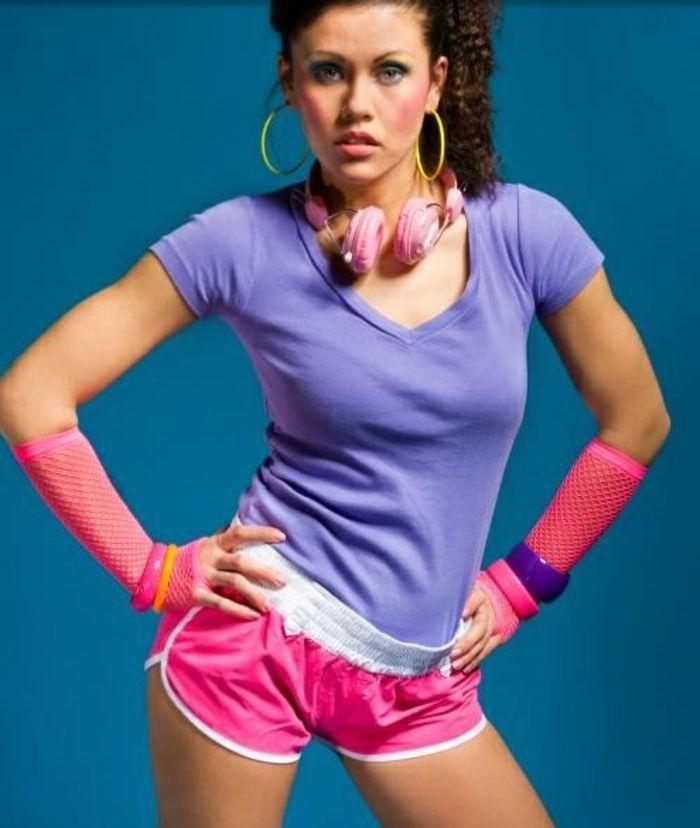 Frau Aus Den 80er Jahren In Sportoutfit Kurze Neonpinke Hose Lila T Shirt Plastikarmbander Netzhandschuhe 80er Kleidung 80er Workout Outfit