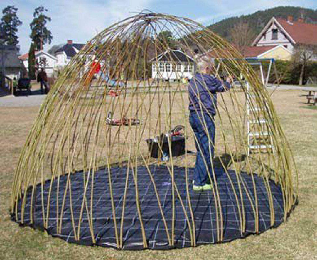 HYTTEBYGGING: Levende pil flettes til hytte, som blir grønn og fin når sommeren kommer.FOTO: PILIHJERTET.NO