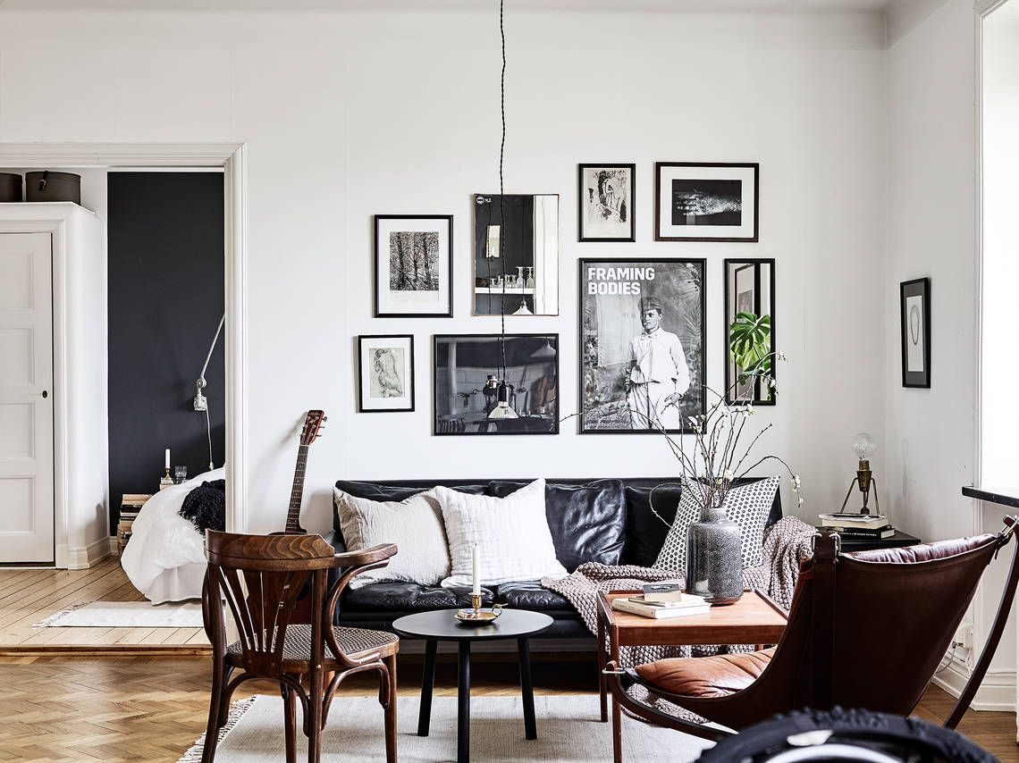 Cozy hipster living room with black leather sofa