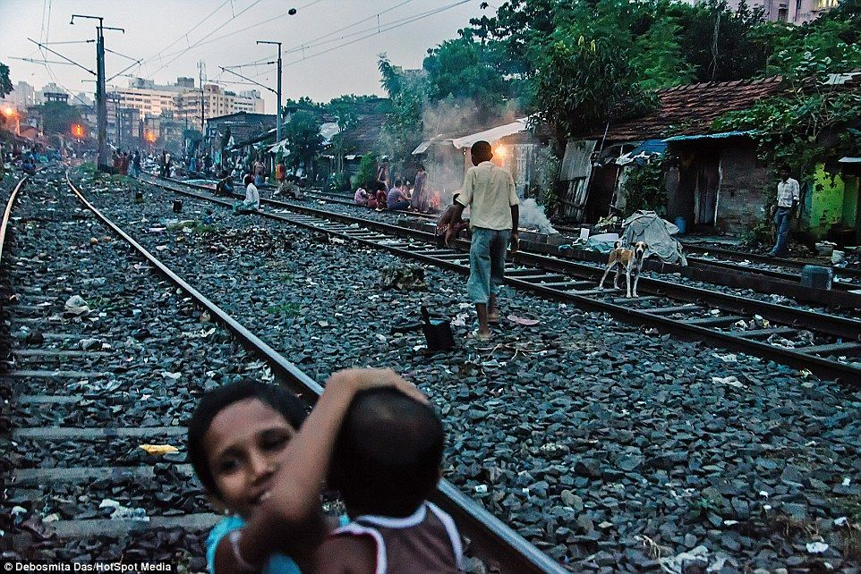 The slum in India where children play on active train tracks