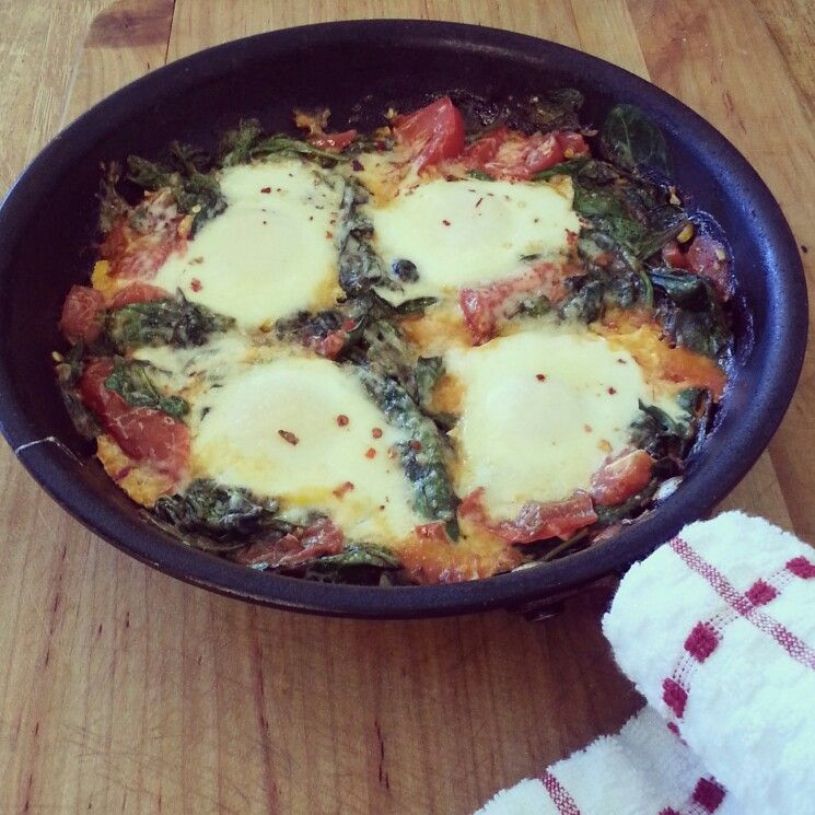 Baked eggs with spinach, tomatoes and garlic. Yum