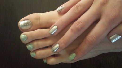 Shiney silver and light green simple nail design. You can do your finger nails opposite one with more green and the other with more silver. Same with your toes. Then just put the opposite color dots going vertically down the nail.