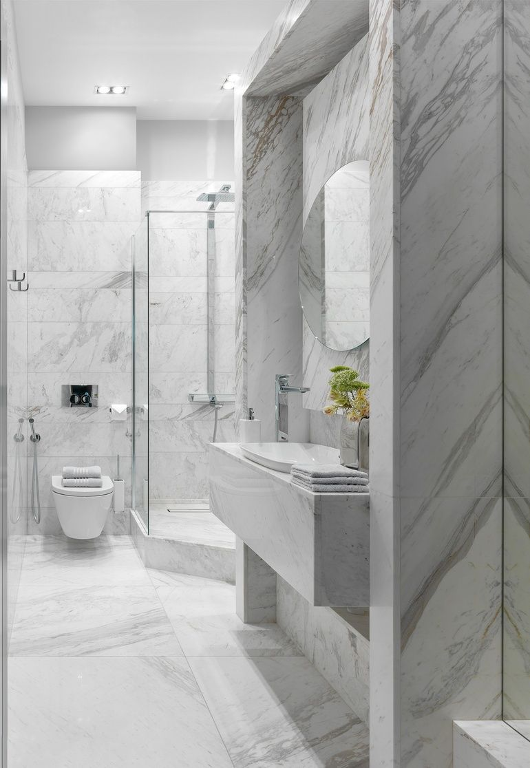 Volakas marble fills the guest bathroom with a laufen toilet and sink and a hansgrohe mixer