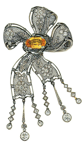 A Belle Epoque platinum, diamond and topaz brooch  Designed as a pierced ribbon bow with central claw-set oval mixed-cut yellow topaz, each ribbon loop with applied old brilliant-cut diamond flowerhead clusters and rose-cut diamond leaf detail, the lower articulated ribbon panel with six diamond line drops, circa 1910, detachable brooch fitting