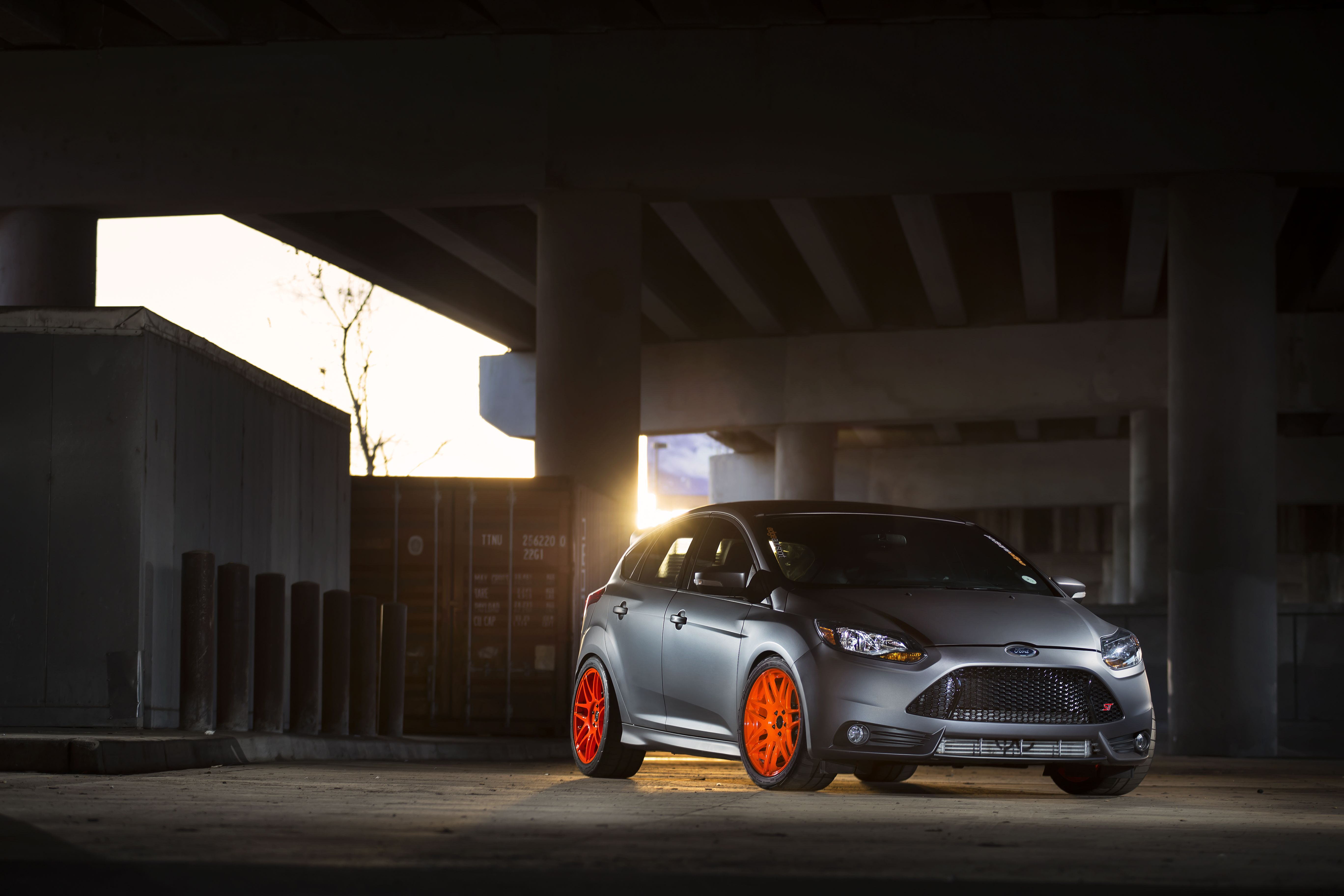 Ford focus st mk3 in moondust silver color with orange alloy wheels under the bridge