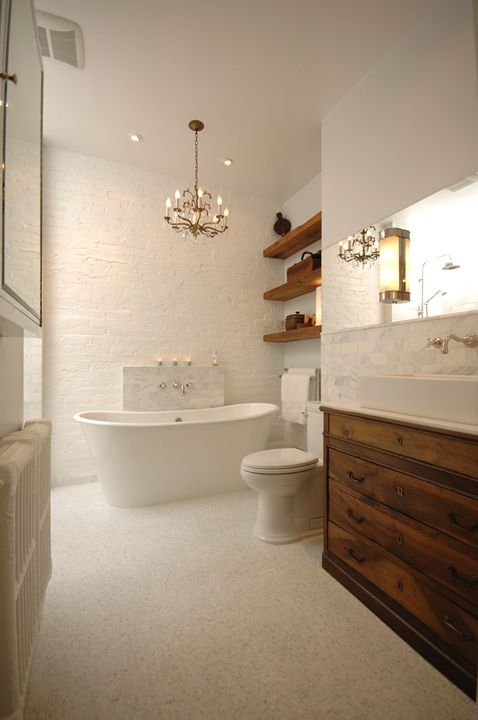 Master bathroom design with white painted exposed brick wall, white soaking tub, polished nickel wall-mount faucet, walnut bathroom cabinet, white carrara marble subway tiles backsplash and rustic wood floating shelves. - Not sure what the flooring is...