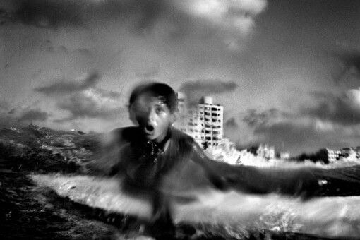 Surfer Momen Abu Assi, 13, catches a wave along the coast of the
