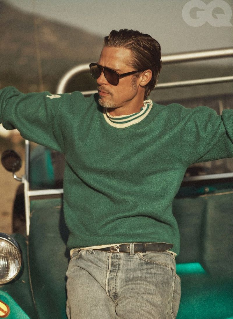 Front and center, Brad Pitt wears a Stock Vintage sweater, POLO Ralph Lauren jeans, a belt by Artemas Quibble, and vintage Ray-Ban sunglasses.
