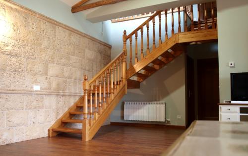 escalera en l de madera con barandas talladas para espacios a