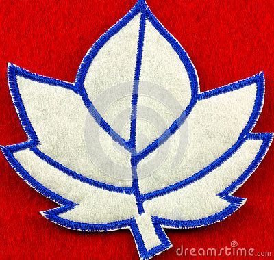 One blue and white stitched felt maple leaf shaped patch on a red background