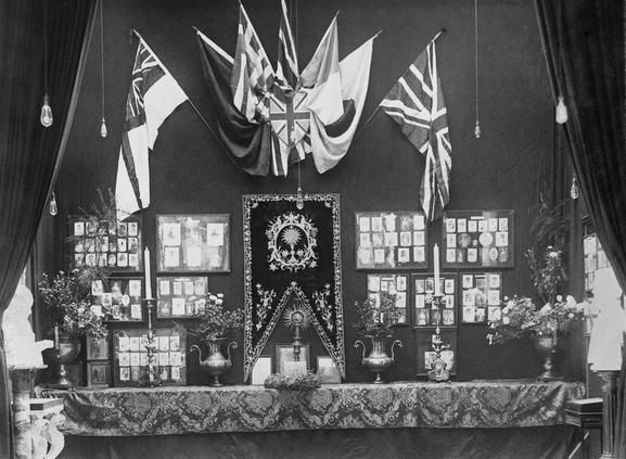 A general view of a Women's War Display at the Women's War Work Exhibition at Whitechapel. Photographs line the wall and flags and candles decorate the display. Horace Nicholls. 1918. IWM Q 31113