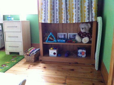 Camilo's bedroom: shelf in corner with toys, books in basket by shelf.