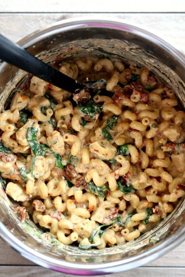 Instant Pot Tuscan Chicken Pasta–curly pasta is enveloped in a creamy parmesan, basil and cream cheese sauce with bites of sun-dried tomatoes, spinach and tender chunks of chicken.