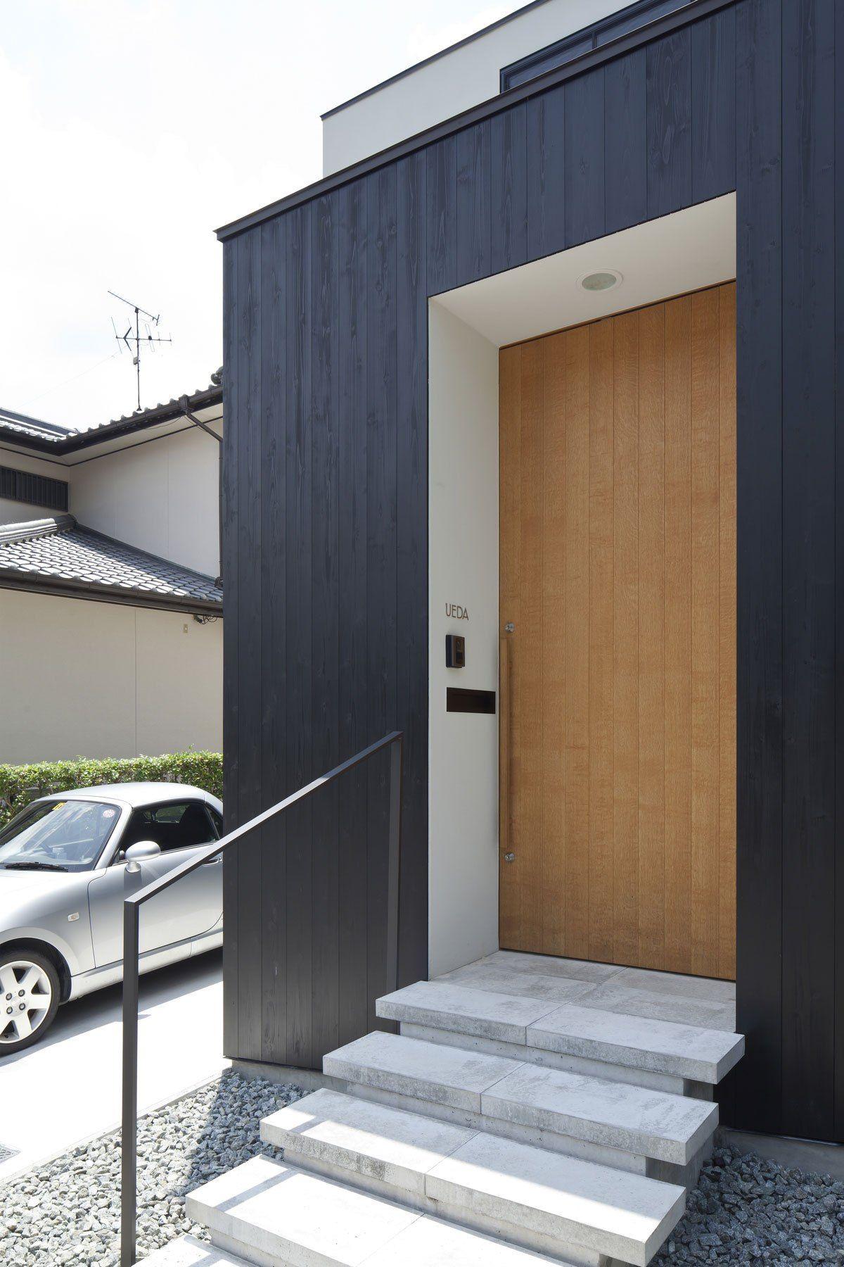 アプローチの床は平板コンクリート 玄関扉は高さ2 6mのナラ練付で製作 小さな中庭 ドアのデザイン 住宅建築