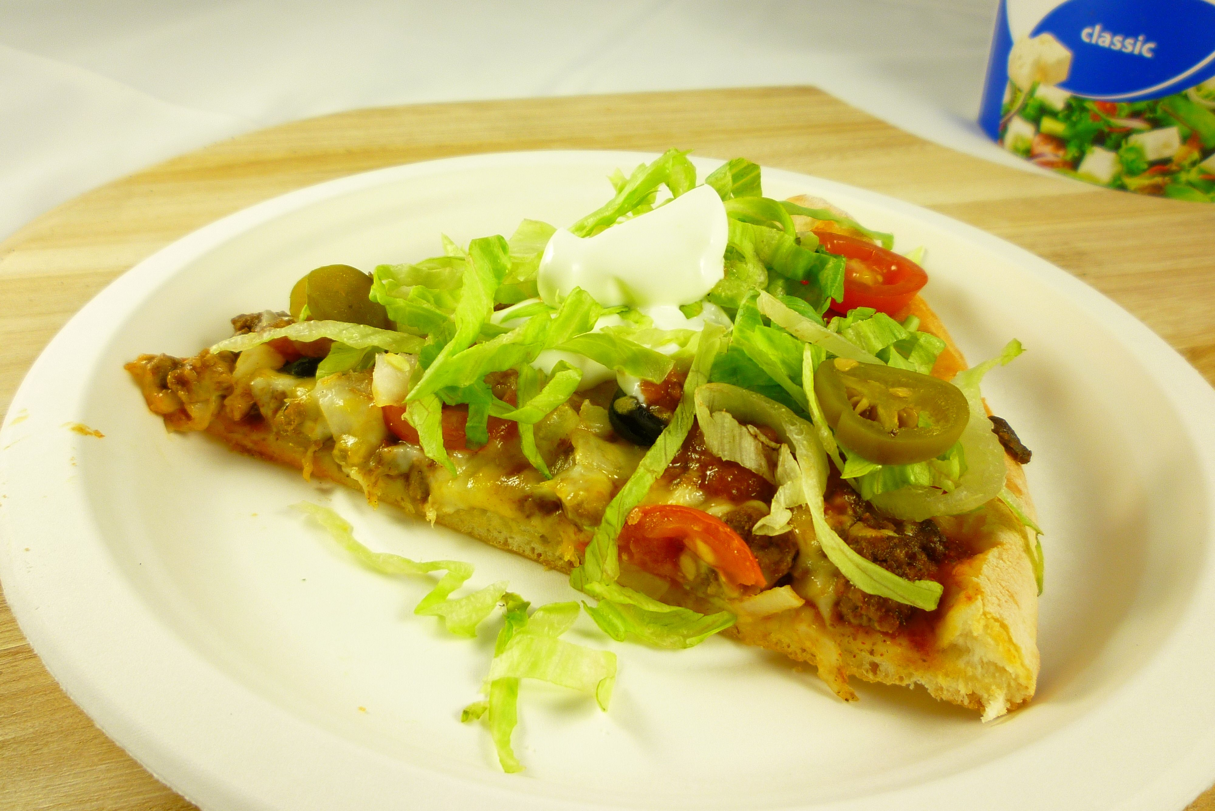 Mexican Pizza slice with lettuce, salsa and sour cream