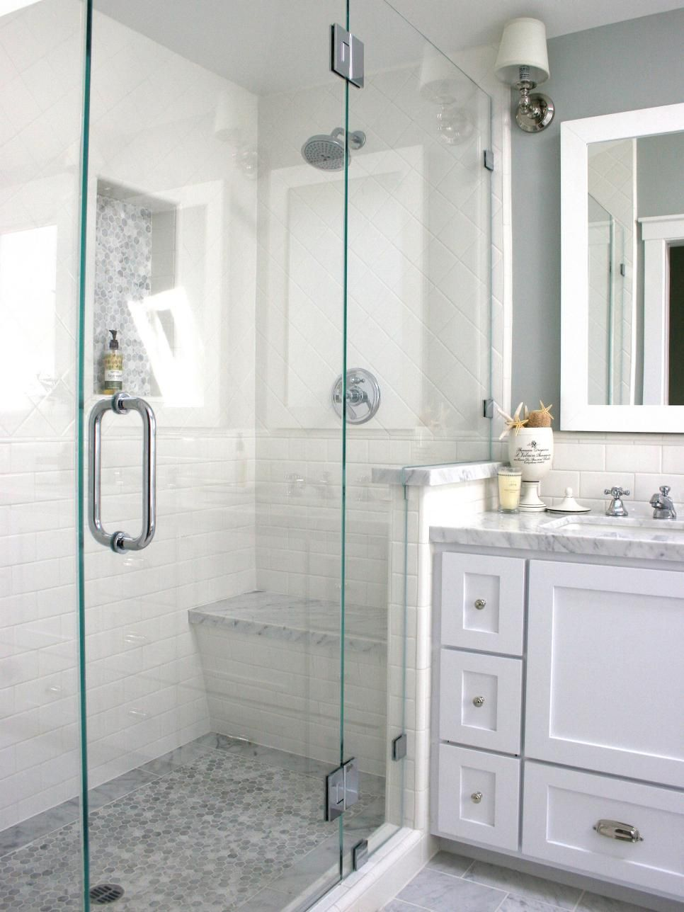 A glass-enclosed shower with white tile walls and a gray mosaic tile ...