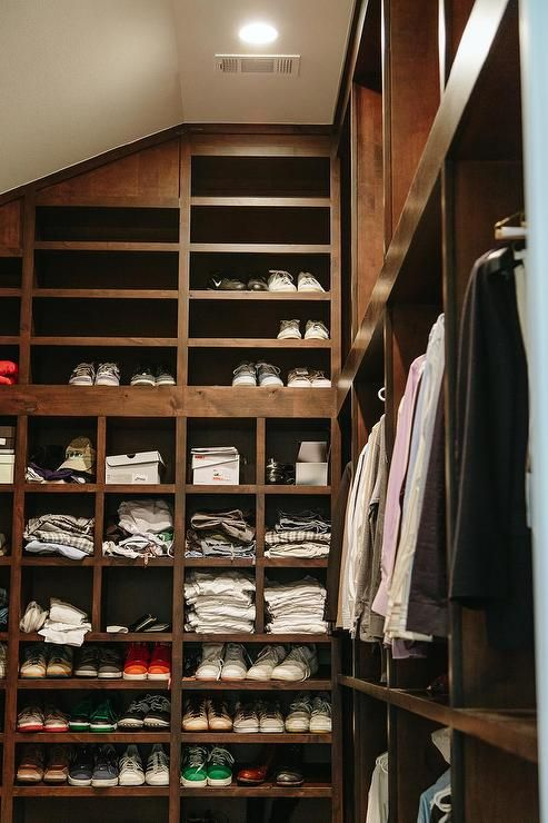 Masculine Walk In Closet Features Dark Stained Floor To Ceiling Shelves  Filled With Shirts And Gym