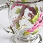 Wooden twigs wrapping around the glass with delicate leaves and small budding flowers. The final touch is elegant gold swirls trailing around the design.