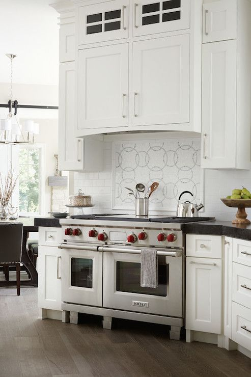 Stunning Kitchen Features White Cabinets Paired With Thick Black Countertops And A Mini Subway Tiled Backsplash Flanking An Angled Stove Wolf Range