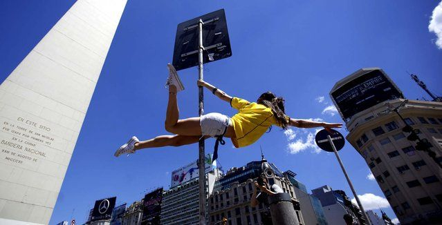 "A dancer performs in the street to promote the ""Miss Pole Dance Sudamerica 2010"" competition to be held Saturday in Buenos Aires, Argentina. (Photo by Natacha Pisarenko/Associated Press) http://avaxnews.net/appealing/Street_Pole_Dancing.html"