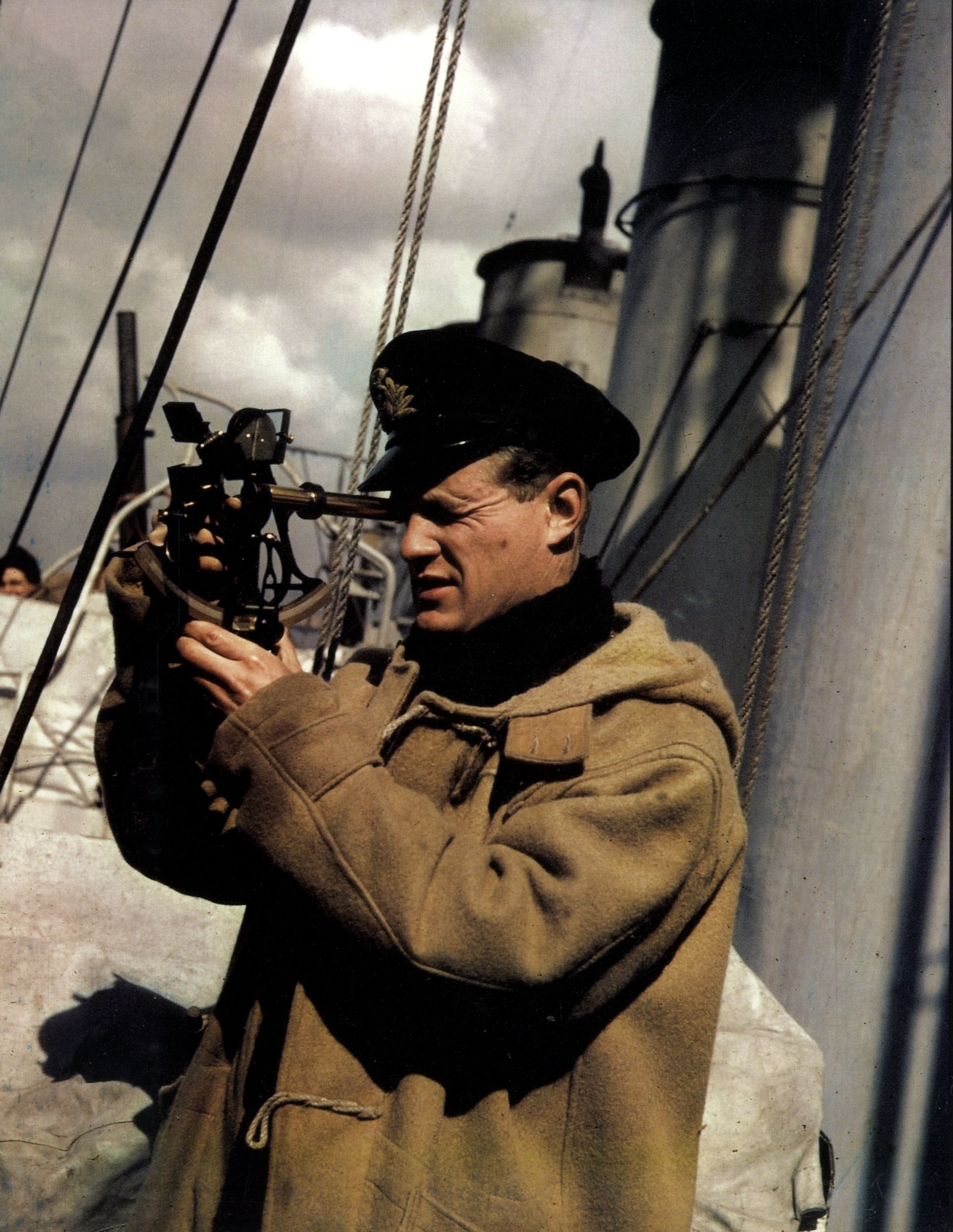 Royal Navy officer takes a bearing with the sextant. He wears the ...