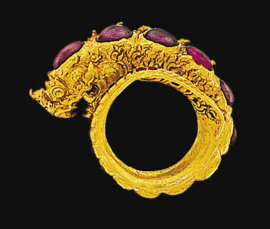 A late 18th/early 19th century heavy gold and ruby 'Naga' ring   In the form of a coiled dragon like creature with chased and engraved detail, closed set with a graduated row of cabochon rubies, with traces of red and white enamel, Siam or Java